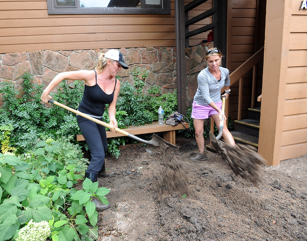 . Jennifer Wittemeyer, left, and Kelly Schultz, shovel out mud at the Farmer\'s Insurance building on West Arapahoe in Boulder. For more flooding videos and photos, www.dailycamera.com. Cliff Grassmick  / September 13, 2013