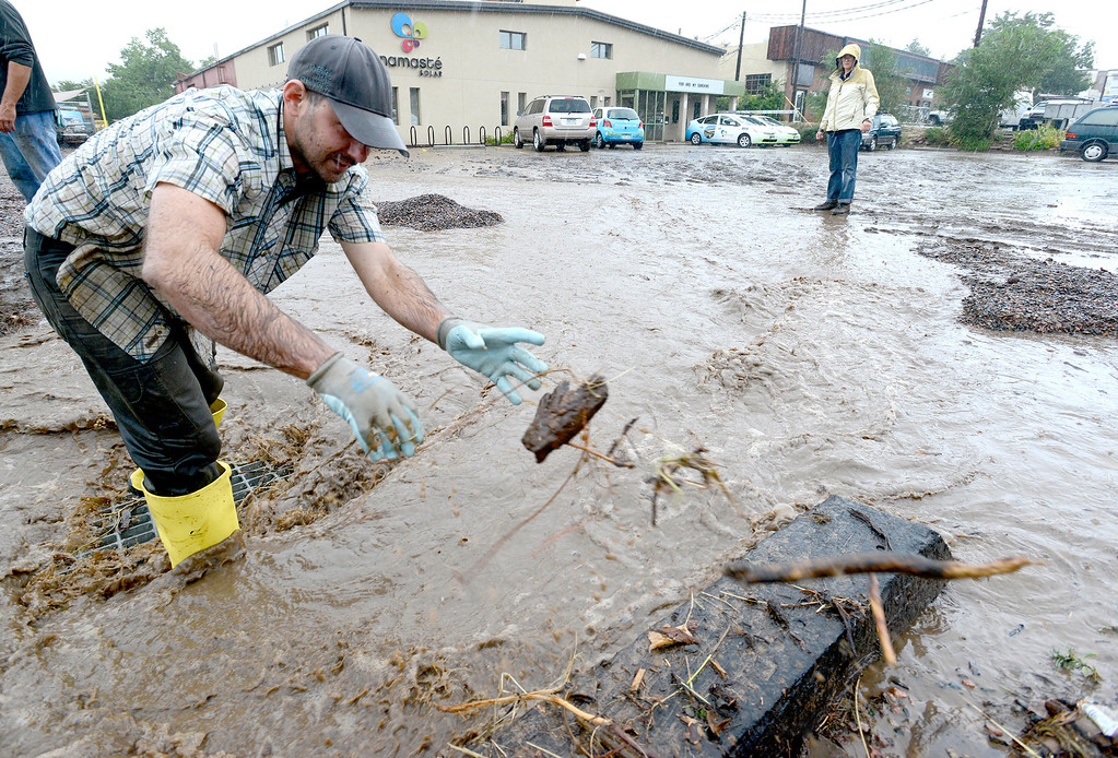. Josh Taylor works to keep the storm grate clear at water runs down the parking lot at Namaste Solar while heavy rains causing heavy flooding in Boulder, Colorado September 12, 2013. BOULDER DAILY CAMERA/ Mark Leffingwell