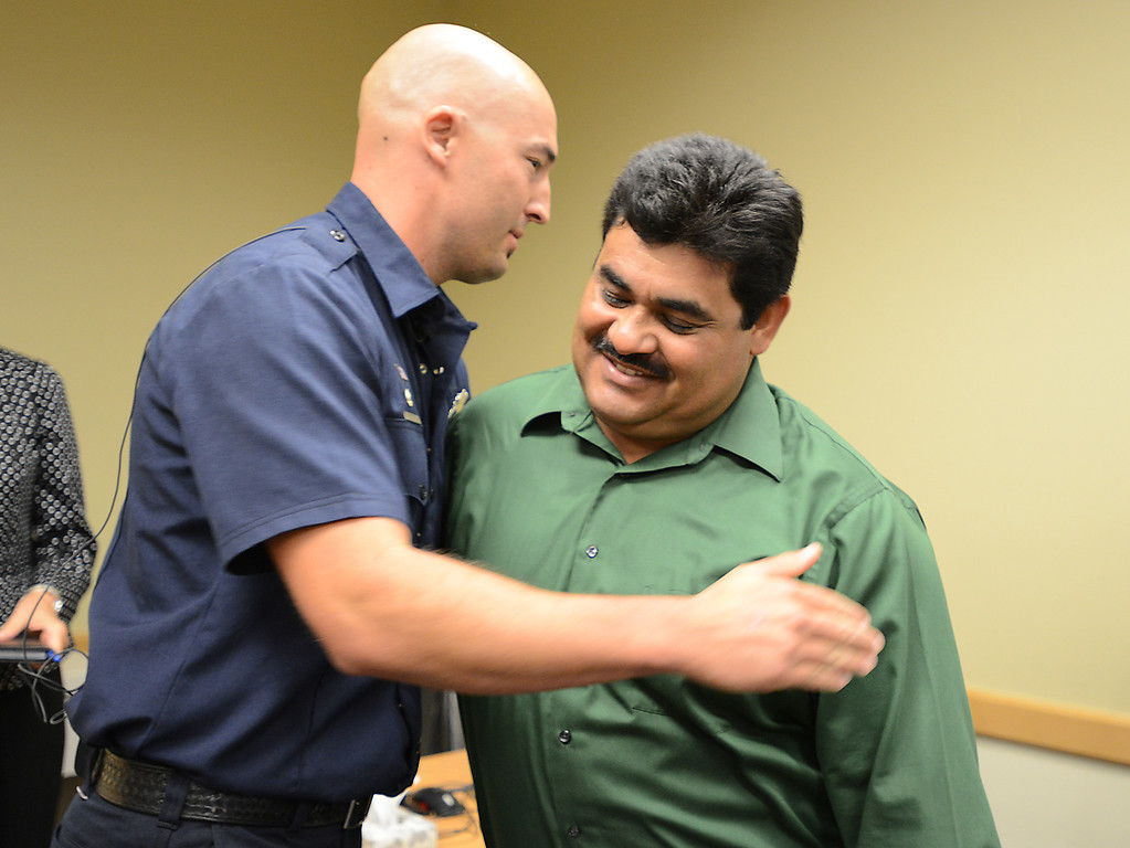 . North Metro Fire Rescue engineer John Cook, left, gives Roy Ortiz a hug after a news conference at Good Samaritan Hospital on Friday. Ortiz was rescued from being trapped in the water by Cook on Thursday after Oritz and his  car plunged into the creek at Dillon Road east of US 287.  September 13, 2013 staff photo/ David R. Jennings