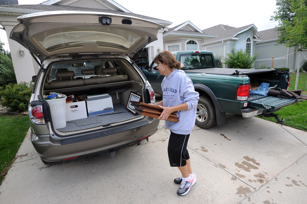 . Judy Laursen helps a neighbor load belongings in a car in the Champion Neighborhood in Longmont, Colorado on September 14, 2013. Residents were allowed in for an hour to get belongings on Saturday. Cliff Grassmick / September 14, 2013