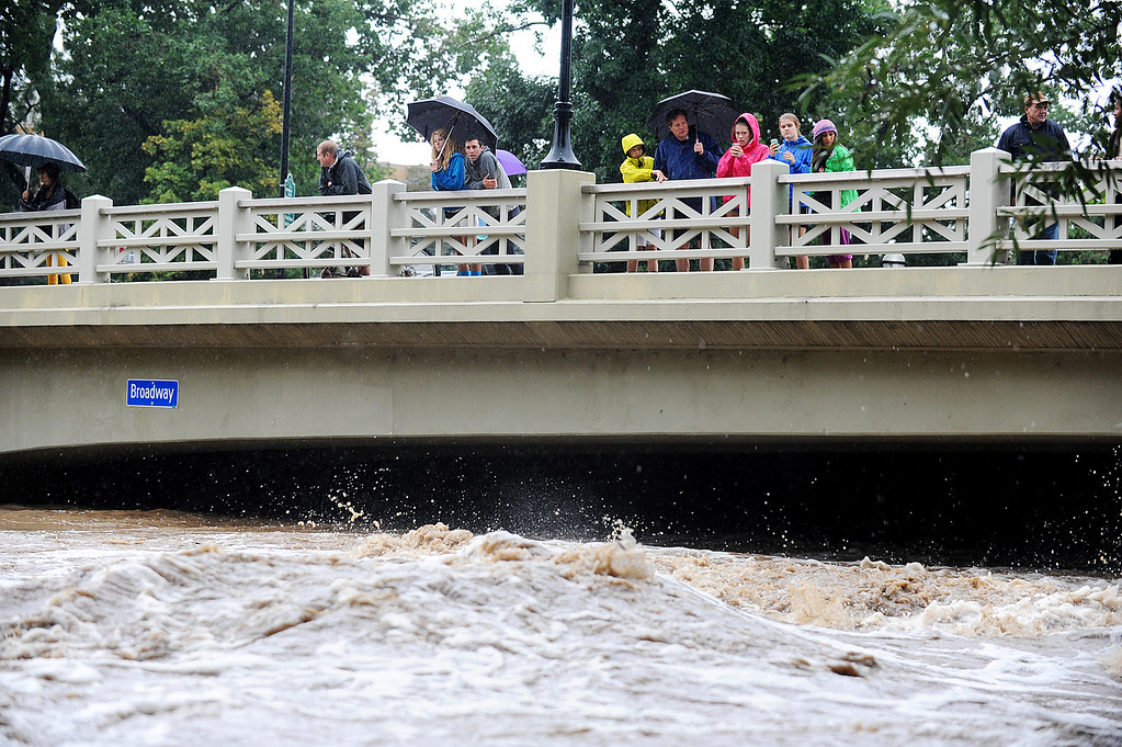. People watch from the Broadway Street bridge in Boulder as the Boulder Creek rises on Thursday, September 12, 2013. (Kira Horvath/ Daily Camera)