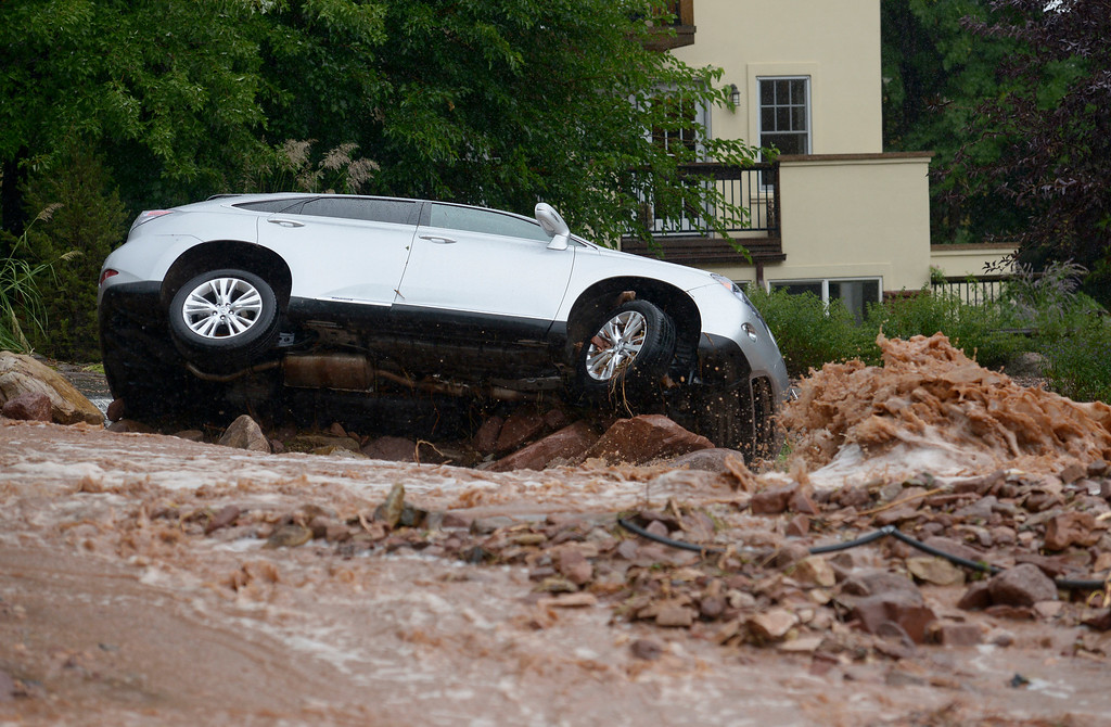 . A car is overturned on Linden Street during the heavy flooding on Thursday in Boulder. For a video of the flooding go to www.dailycamera.com  Jeremy Papasso/ Camera