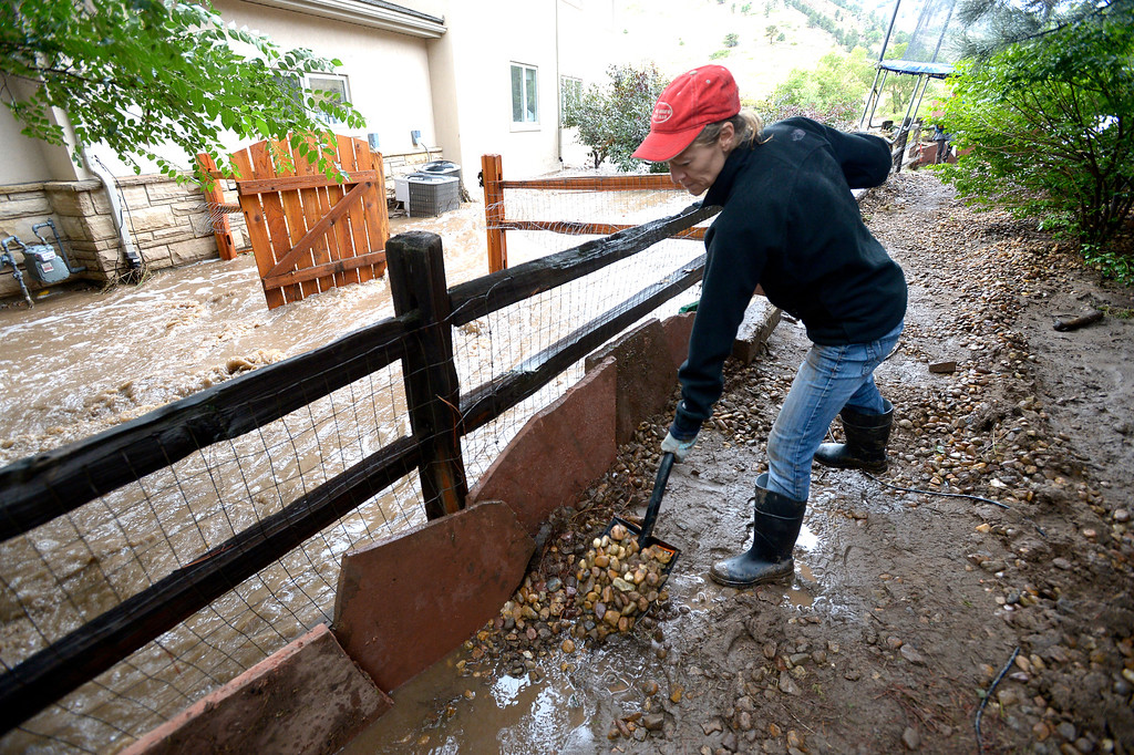 . Nicole Thomas use rocks and patio stones to hold back the water from  their home off Lee Hill Drive in Boulder on Friday.  Photo by Paul Aiken