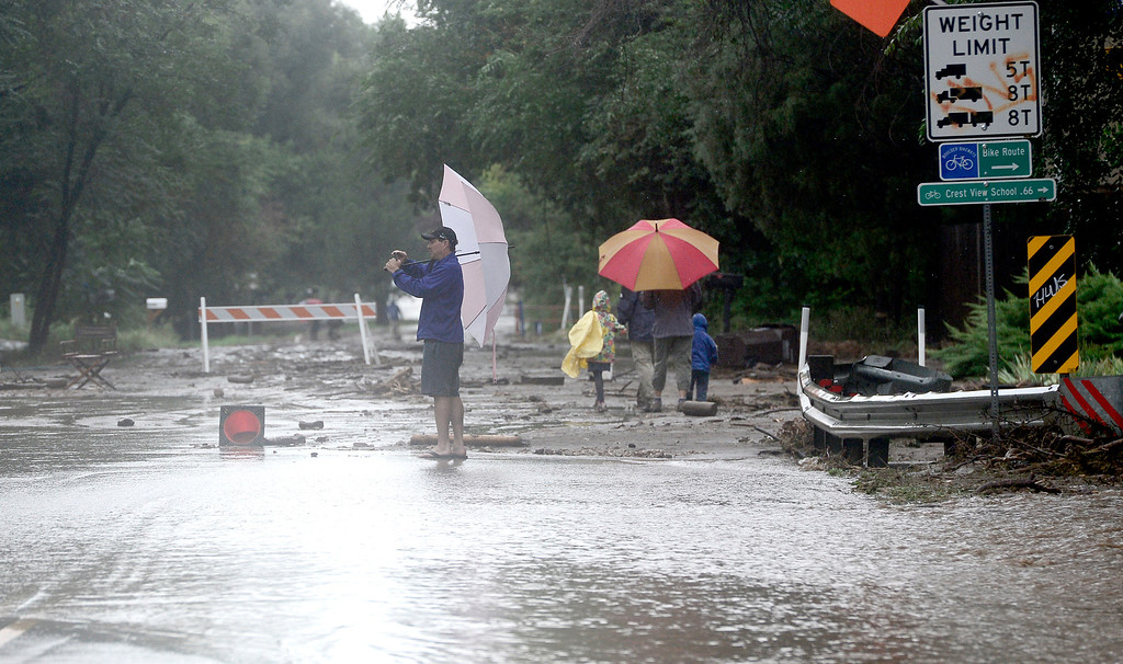 . A man takes photos of the damage from heavy rains in Boulder, Colorado September 13, 2013. BOULDER DAILY CAMERA/ Mark Leffingwell