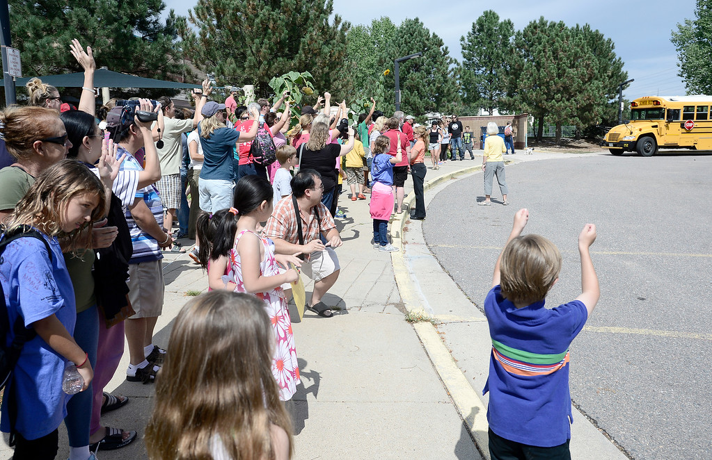 . Families cheer as a bus carrying several Fireside Elementary 5th grader who were trapped at Camp-Calwood comes in the the school in Louisville, Colorado September 14, 2013. Over 80 Fireside 5th graders were trapped by flooding above Jamestown.  BOULDER DAILY CAMERA/ Mark Leffingwell
