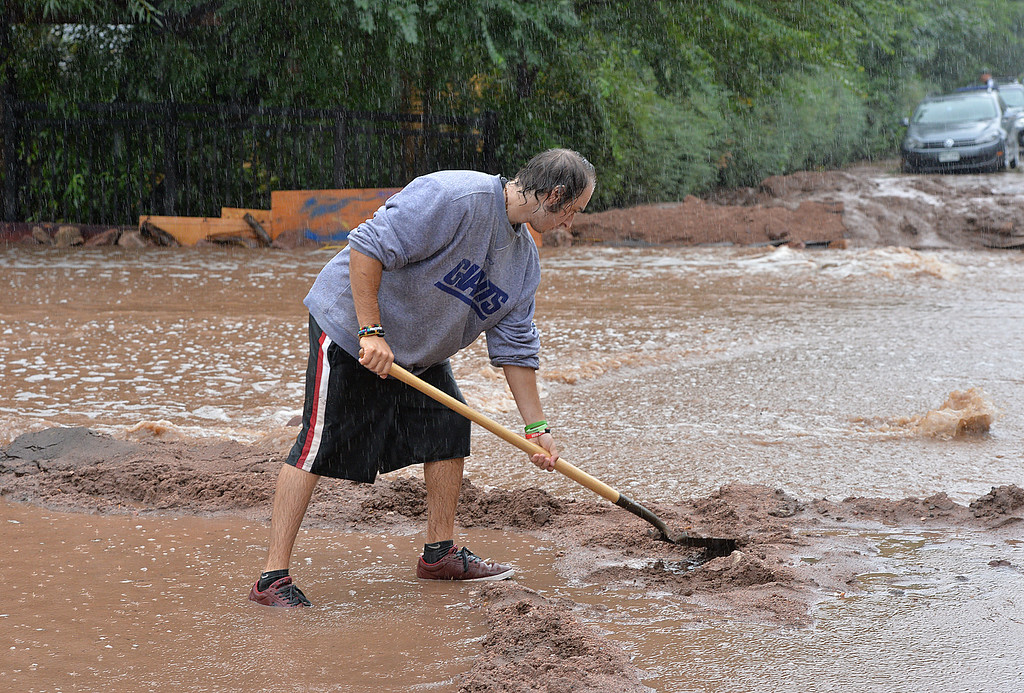 . Ameen Batah uses a shovel to help relieve flooding along Mariposa Ave. and 20th in Boulder on Thursday. September 12, 2013 staff photo/ David R. Jennings