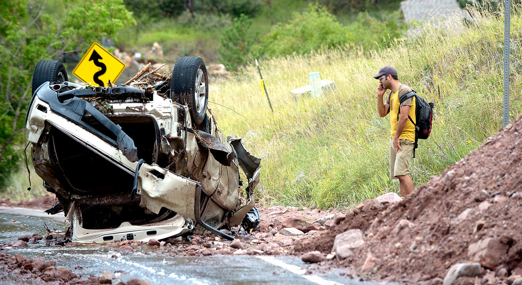 . Greg Leon looks over an overturned car in Pine Brook Hills on Friday September 13, 2013 ....Photo by Paul Aiken / The Daily Camera
