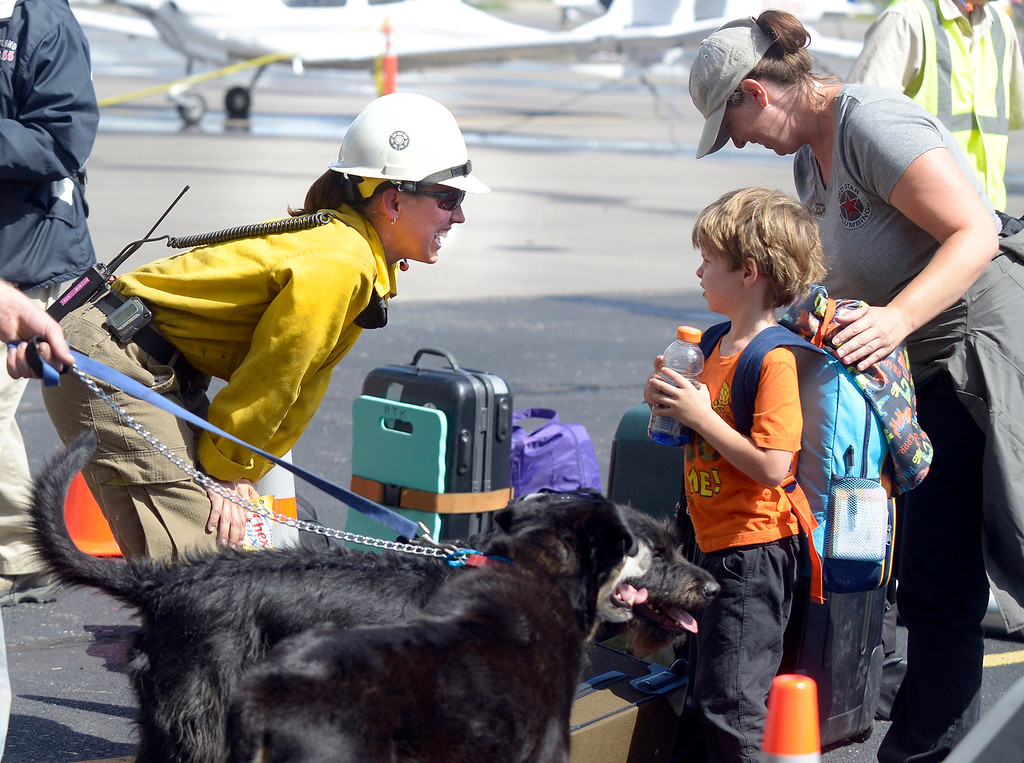 . A rescue worker, at left, talks with a young boy after he and his family were rescued by helicopter from the flooded areas on Monday, Sept. 16, at the Boulder Municipal Airport in Boulder. For more photos and video of the flood rescue go to www.dailycamera.com Jeremy Papasso/ Camera