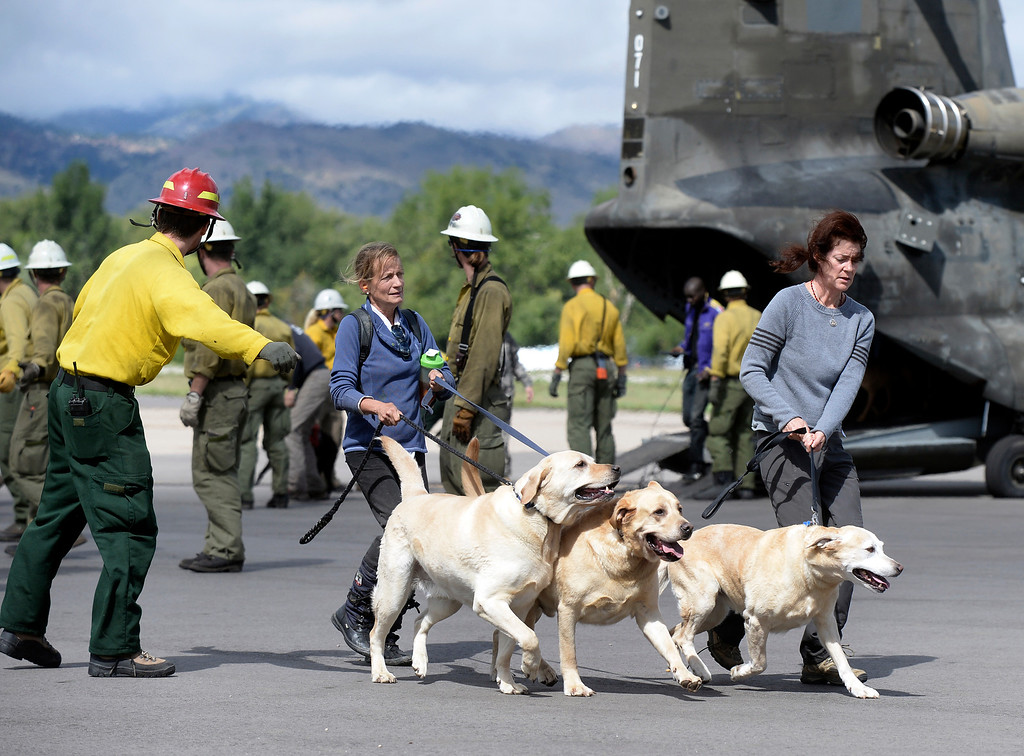 . Evacuees walk across the tarmac after being rescued by helicopter from the Pinewood Springs area on Monday, Sept. 16, at the Boulder Municipal Airport in Boulder. For more photos and video of the flood rescue go to www.dailycamera.com Jeremy Papasso/ Camera