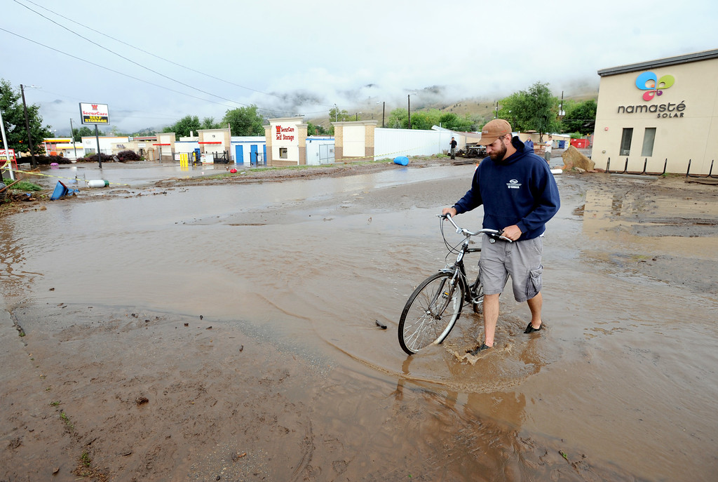 . Brian Frenz of Namaste Solar walks his bike through the water on Friday. For more flooding videos and photos, www.dailycamera.com. Cliff Grassmick  / September 13, 2013