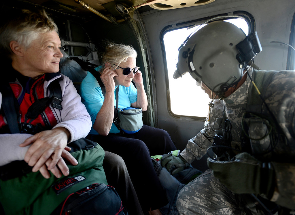 . Staff Sergeant Jose Pantoja (R), with the 2-4 GSAB 4th Infantry Division based in Ft. Carson, checks on two women his crew rescued near Jamestown, Colorado September 17, 2013. BOULDER DAILY CAMERA/ Mark Leffingwell