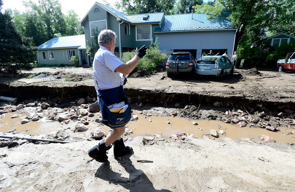 . US Postal Service Letter Carrier Mike Posniewsky looks to deliver mail across a washed out Topaz Drive in Boulder on Saturday September 14, 2013. Photo by Paul Aiken / The Daily Camera / Saturday September 14, 2013