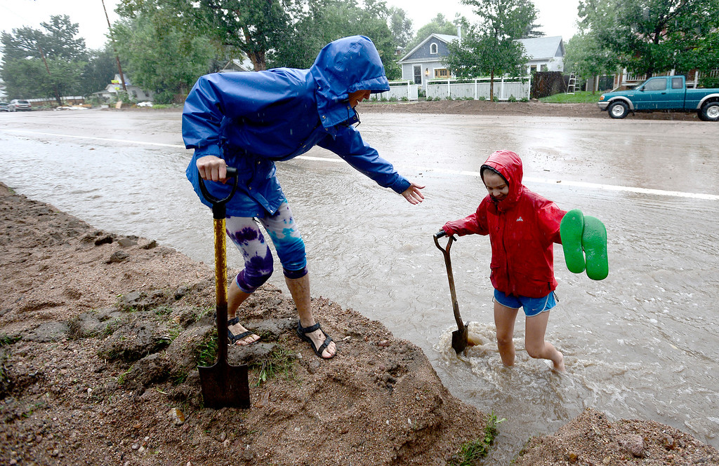 . Wendy Hoffenberg (L) helps Sophia Cornell up to the side walk as rain get heavy and water begins to rise in Boulder, Colorado September 15, 2013. REUTERS/Mark Leffingwell  (UNITED STATES)