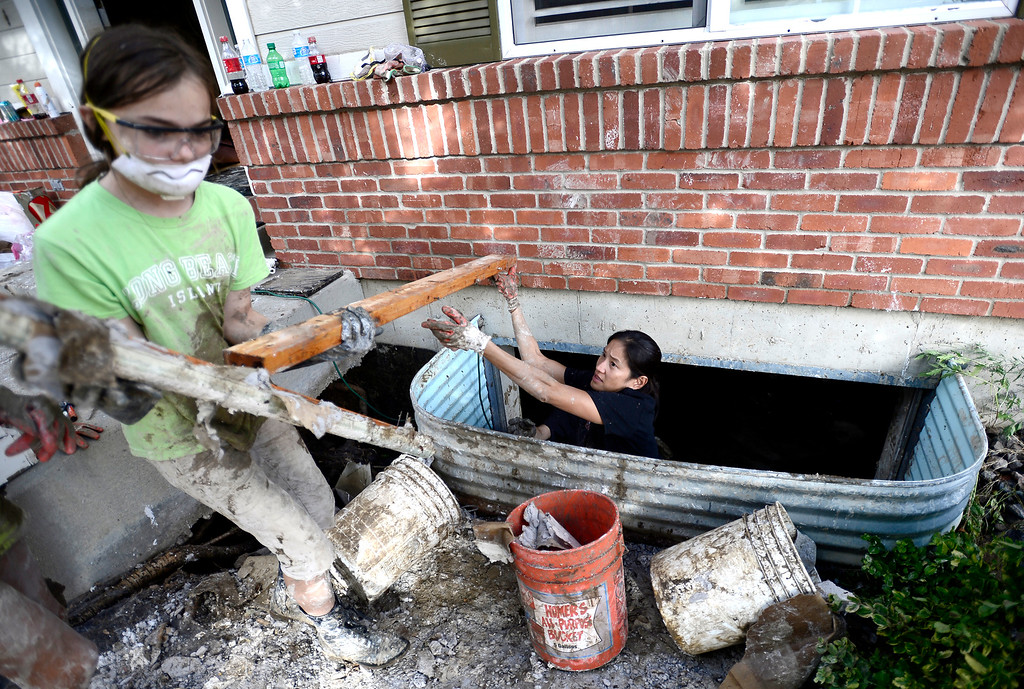 . Birdie Reznickek (right), neighbor, passes wood from the ruined basement to Kate McCarthy (left), 11, as they work to clean up the flood damage in McCarthy\'s home on Qualla Drive in Boulder, Colorado September 14, 2013. BOULDER DAILY CAMERA/ Mark Leffingwell