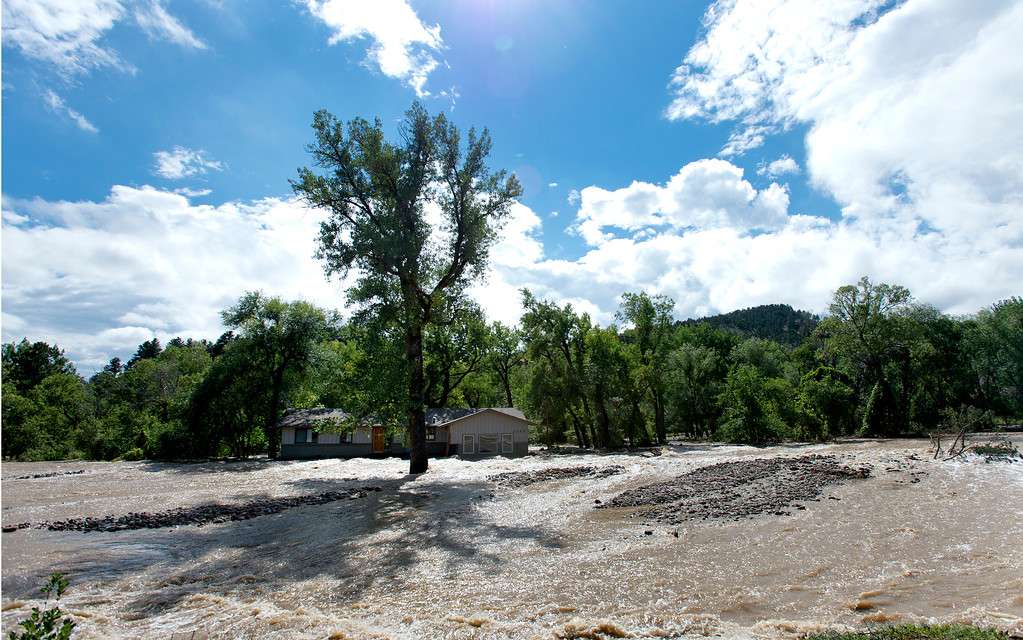 . A home sits with water from Left Hand Creek running on both sides in Boulder, Colorado September 16, 2013.  DAILY CAMERA/ MARK LEFFINGWELL