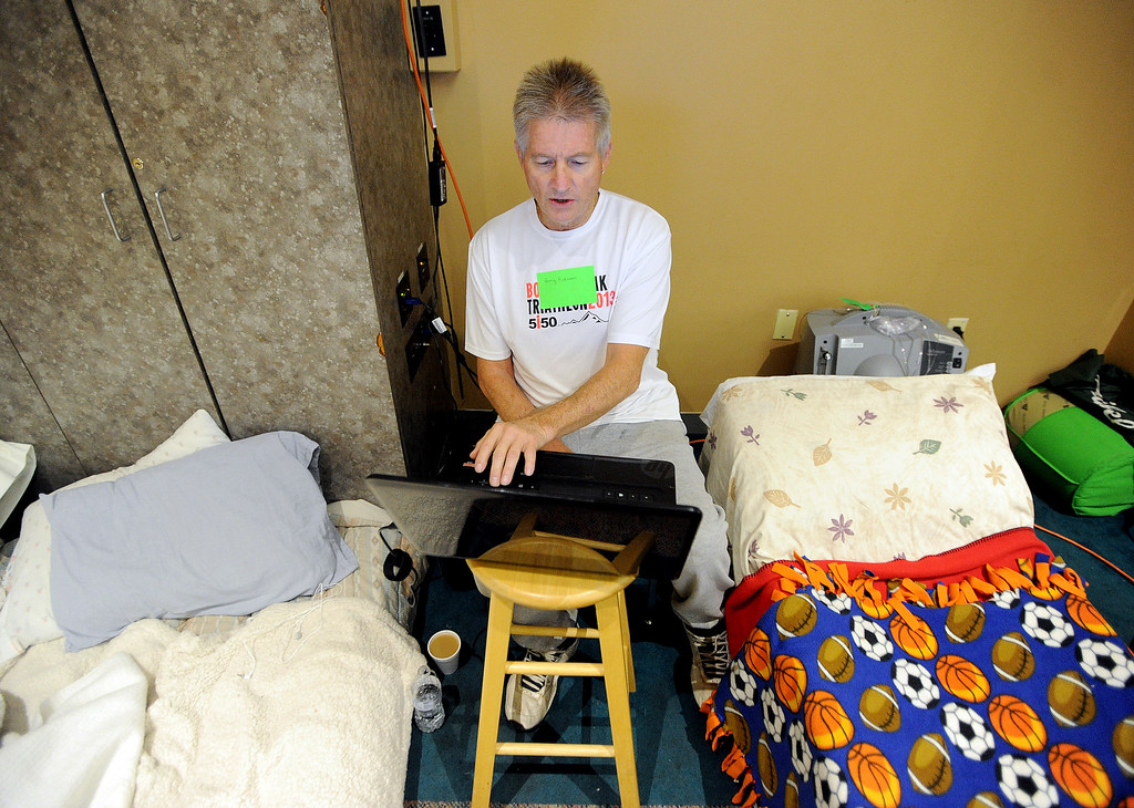 . Gary Peterson, of Lyons, uses his computer to check the conditions around his home. He is staying at the LifeBridge Church in Longmont, Colorado on September 15, 2013. Cliff Grassmick / September 15, 2013