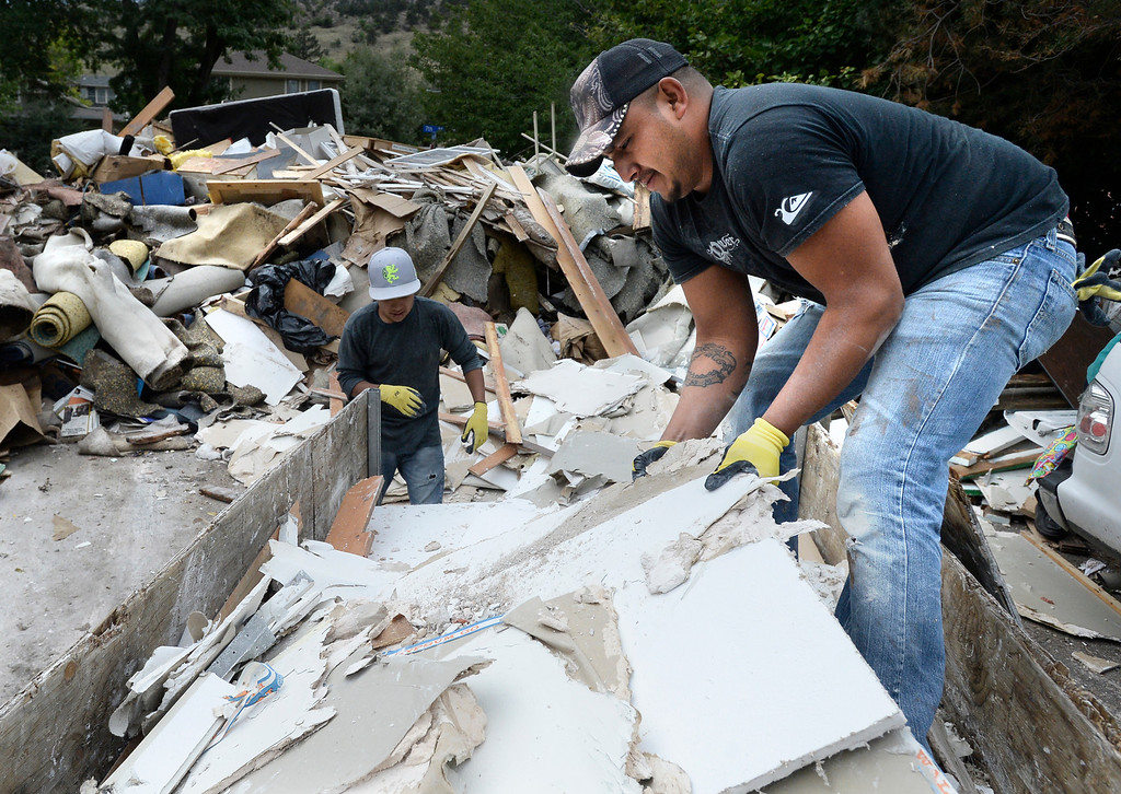 . Giovanni Lara, at right, and Geraldo Lara dump flood damaged drywall from their Boulder apartment into a massive pile of damaged belongings at the North Boulder Park on Wednesday, Sept. 18, in Boulder. For more photos and video of the flood go to www.dailycamera.com Jeremy Papasso/ Camera