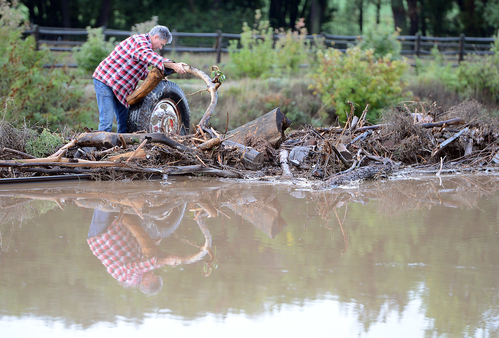 . A resident at a farm south of Longmont, clears debris from the railroad tracks near his land on Friday morning. For more flooding videos and photos, www.dailycamera.com. Cliff Grassmick  / September 13, 2013