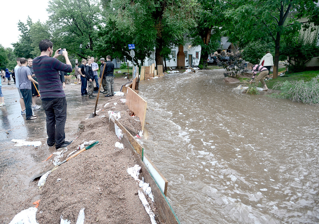 . Neighbors got together shoveling wash out debris into a dyke to funnel water down 7th Street at Arapahoe as heavy rains cause severe flooding in Boulder, Colorado September 12, 2013. BOULDER DAILY CAMERA/ Mark Leffingwell