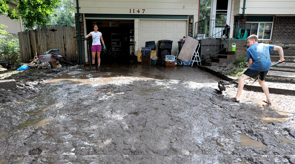 . Stefani Anderson, left, and her son Gabe,  clean mud out of the garage of their home on Lefthand Drive in Longmont, Colorado on September 14, 2013. Cliff Grassmick / September 14, 2013
