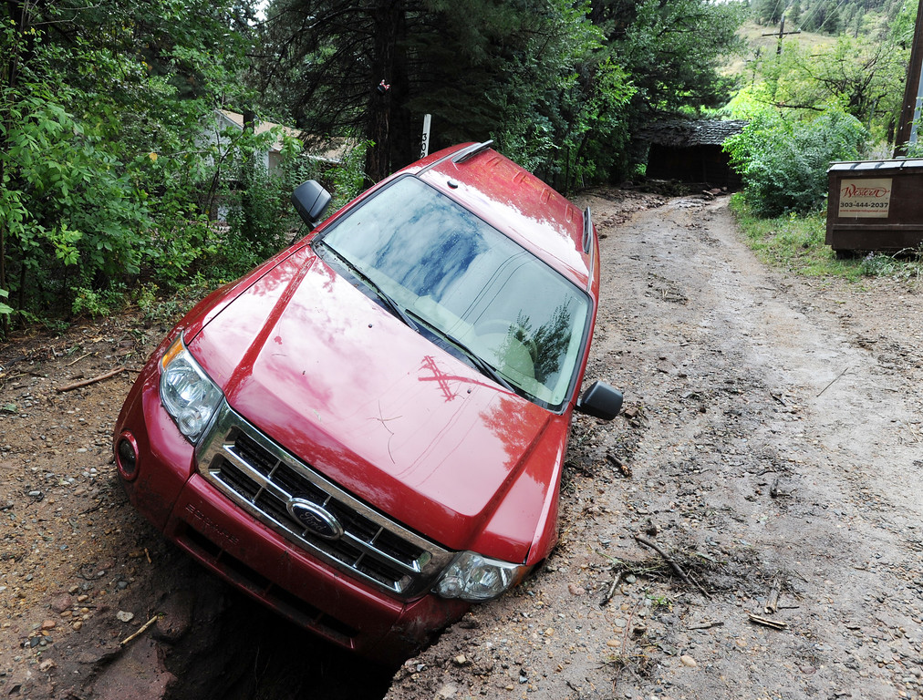 . A car is stuck in a wash out in front of an old wooden shack that washed down a road behind this scene near 3rd and Arapahoe Rd in Boulder. For more flooding videos and photos, www.dailycamera.com. Cliff Grassmick  / September 13, 2013