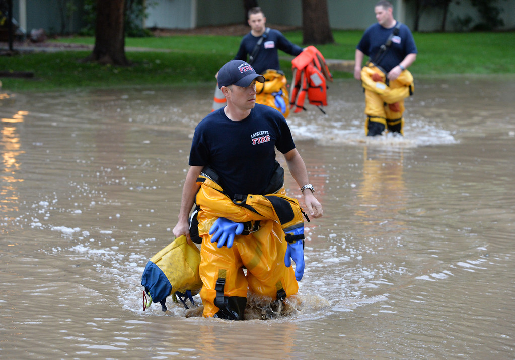 . Lafayette Fire firefighters wade back to dry land to stand by to help in an non voluntary evacuation of the Centaur Crcle area in Lafayette  on Thursday. September 12, 2013 staff photo/ David R. Jennings