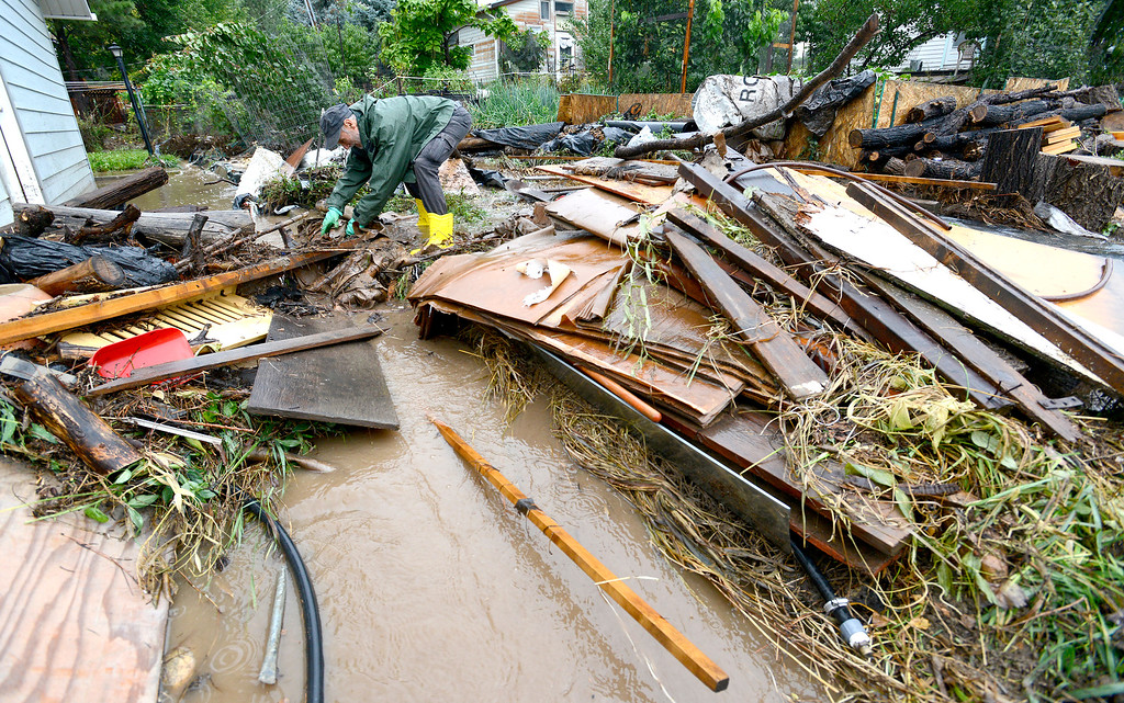 . A man (requested his name not be used) tries to untangle debris what washed down to his home after heavy rains caused severe flooding in Boulder, Colorado September 12, 2013. BOULDER DAILY CAMERA/ Mark Leffingwell