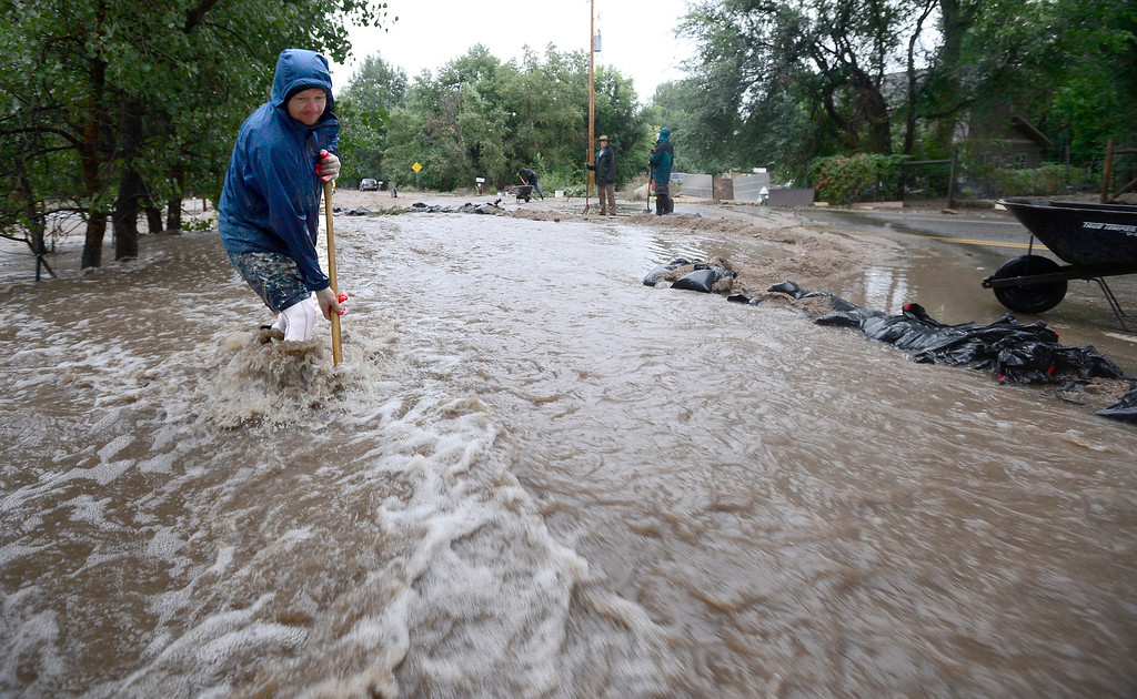 . Dean Beacom digs to keep channel clear in front of sand back dam protecting his home on Violet in Boulder, Colorado September 15, 2013. BOULDER DAILY CAMERA/ Mark Leffingwell