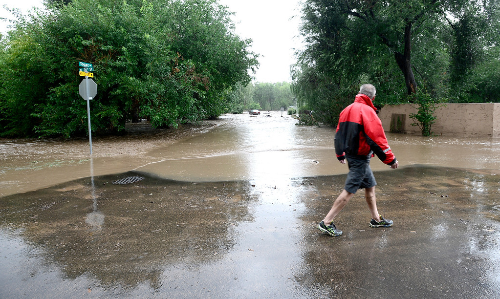 . A man walks by Topaz on 26th watching the water pour down Topaz street from heavy rains in Boulder, Colorado September 12, 2013. BOULDER DAILY CAMERA/ Mark Leffingwell