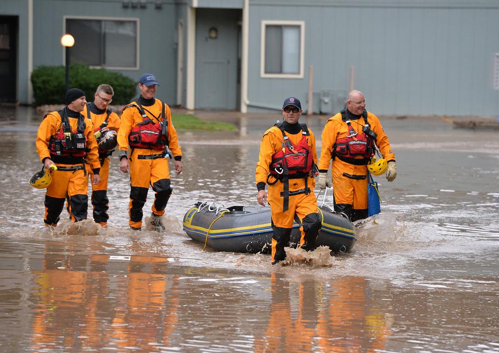 . North Metro Fire Rescue firefighters wade back to dry ground after assisting to help in a non voluntary evacuation of the Centaur Circle area in Lafayette  on Thursday. September 12, 2013 staff photo/ David R. Jennings