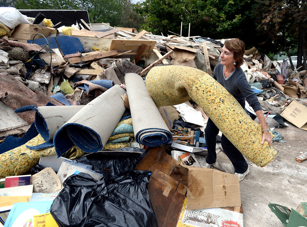 . Trudy Nickola, of Boulder, throws carpet pad into a massive pile of flood damaged property at the North Boulder Park on Wednesday, Sept. 18, in Boulder. For more photos and video of the flood go to www.dailycamera.com Jeremy Papasso/ Camera