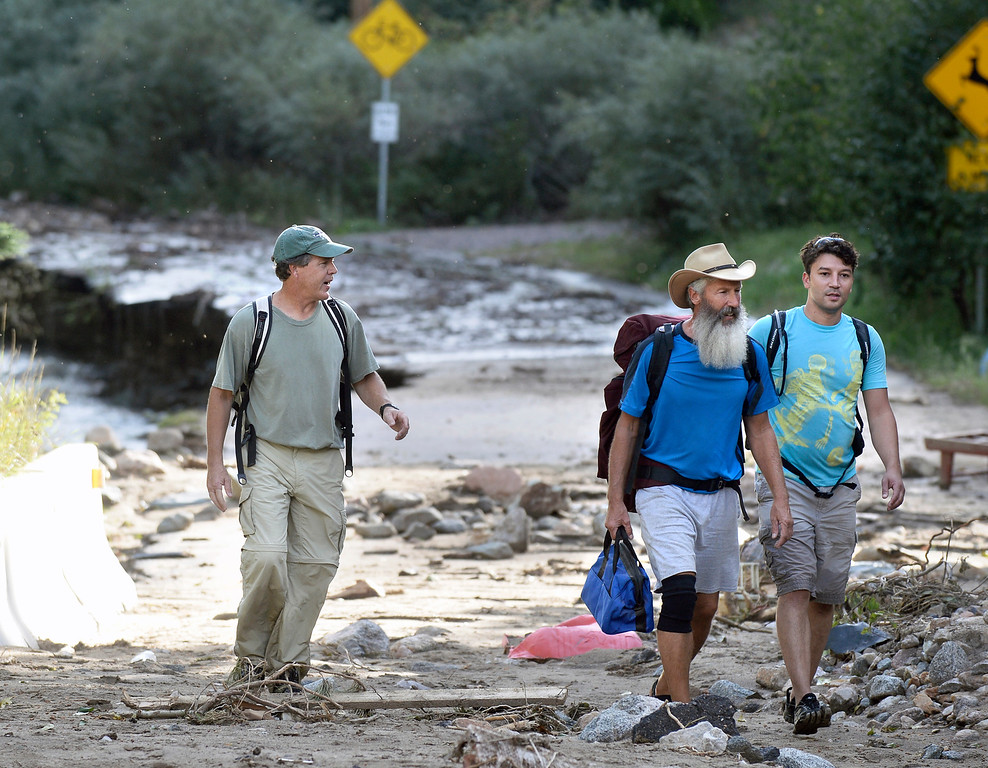 . Fourmile Canyon Drive residents Drew McConaughy, left, and Jeff Holland, walk with their friend Marcus Vann after hiking to see if their homes survived the flood on Tuesday, Sept. 17, in Salinas  in the Fourmile Canyon area of Boulder County. For more photos and video of the flood rescue go to www.dailycamera.com Jeremy Papasso/ Camera