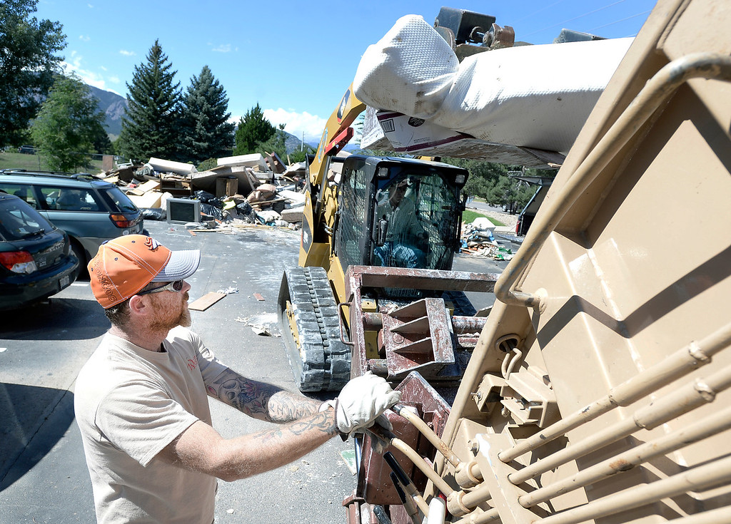 . Western Disposal Services worker Derek Overby, at left, works with Mark Bishop, of Keeter Trucking and Escavating, to pick up flood damaged property on Wednesday, Sept. 18, in Boulder. For more photos and video of the flood go to www.dailycamera.com Jeremy Papasso/ Camera