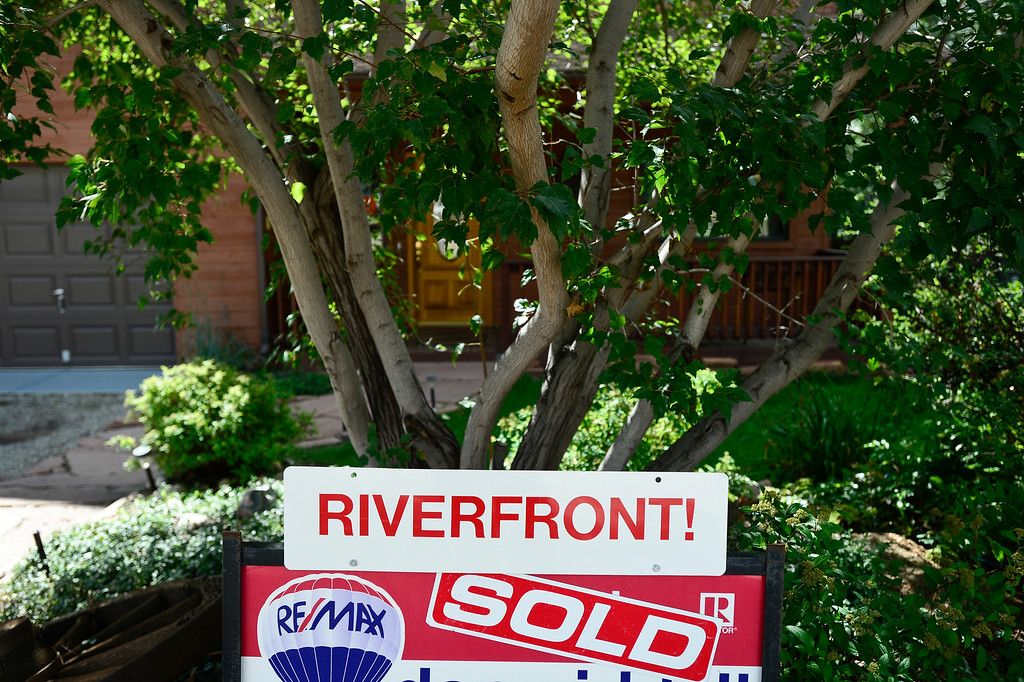 """. A Re/Max sign with a sold sticker is seen in front of a house on Park Drive, Wednesday, Sept. 18, 2013, in Lyons. The house had an orange emergency search sticker with the word \""""unstable\"""" printed on it warning residents to stay out. (Matthew Jonas/Times-Call)"""