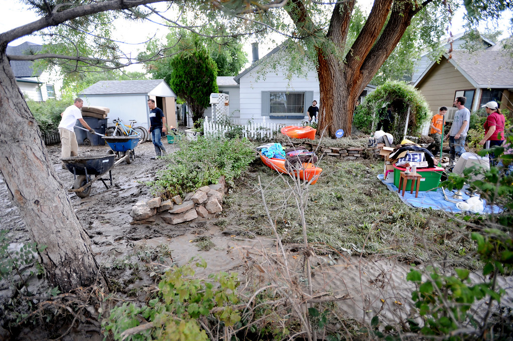 . Friends and family work to clean up the flood damage at their home at 1st Ave. and S. Bowen, in Longmont, during the morning of September 14, 2013. Cliff Grassmick / September 14, 2013