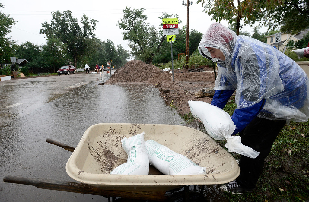 . Aaron Hoffenberg loads a wheel barrow with stand bags to try and block water running over 7th and University in Boulder, Colorado September 15, 2013. REUTERS/Mark Leffingwell  (UNITED STATES)