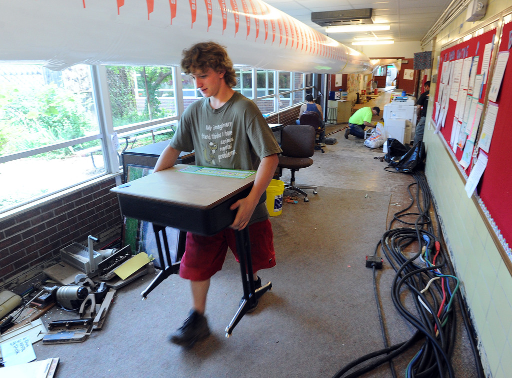 . Ben Stimson relocates a desk at Crest View Elementary in Boulder. Workers from Servpro and other disaster clean up contractors work on flood Damage at Crest View Elementary in Boulder on September 17, 2013. For more flooding videos and photos, www.dailycamera.com. Cliff Grassmick  / September 17, 2013