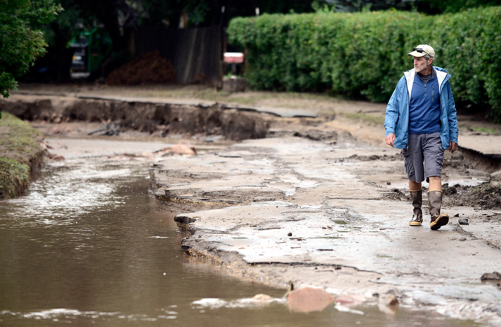 . Anthony Crone walks down Topaz Drive in Boulder, Colorado on Sunday September 15, 2013.  A stream now flows where the road used to be.  Rain fell heavily again today increasing fears of more flooding in the community.  Photo by Paul Aiken / The Daily Camera / Saturday September 15, 2013