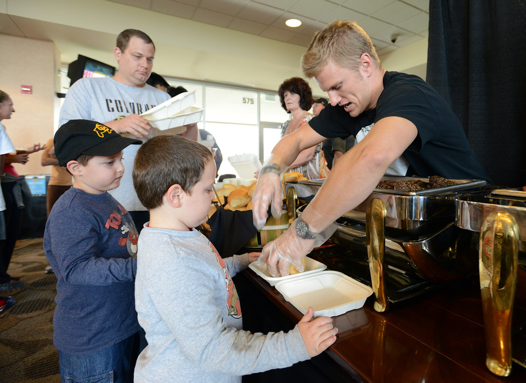 . Amit Davidovich, 6, left, and his twin brother Noam are served hamburgers by Wes Christensen, CU football player, for the residents of CU�s Family Housing in the Club Room at Folsom Stadium on Saturday due to the postponement of the football game.  September 14, 2013 staff photo/ David R. Jennings