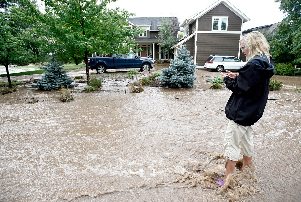 . Carolyn Hornung stands in running water in front of her house calling friends to let them know she is OK after heavy rains caused flooding in Boulder, Colorado September 13, 2013. BOULDER DAILY CAMERA/ Mark Leffingwell