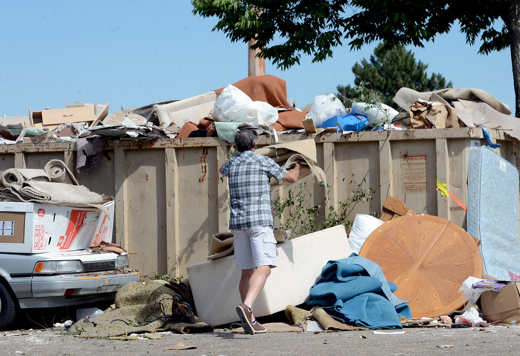 . A man throws away flood debris in a dumpster set out by the City of Boulder at 30th and Mapleton. For more flooding videos and photos, www.dailycamera.com. Cliff Grassmick  / September 17, 2013