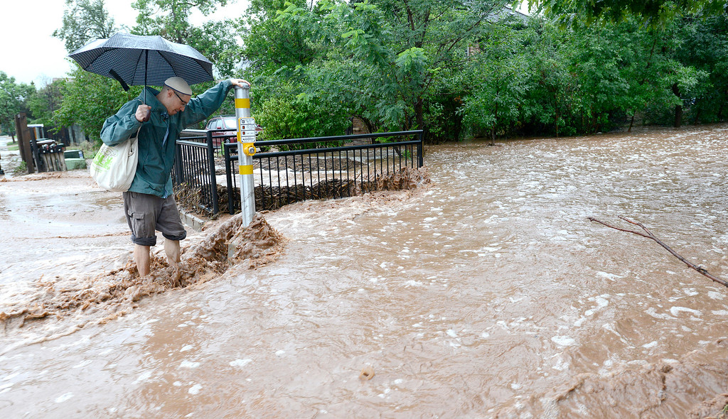 . Matthew Messner looks for a way to cross where water has over flowed the sidewalk from heavy rains in Boulder, Colorado September 12, 2013. BOULDER DAILY CAMERA/ Mark Leffingwell