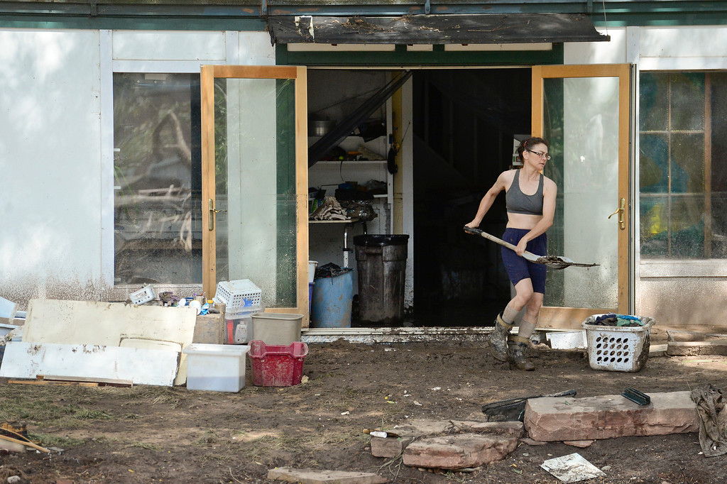 . Cynthia Cappel, of Lyons, shovels mud and debris out of the basement of her house, Wednesday, Sept. 18, 2013, near the St. Vrain River. (Matthew Jonas/Times-Call)