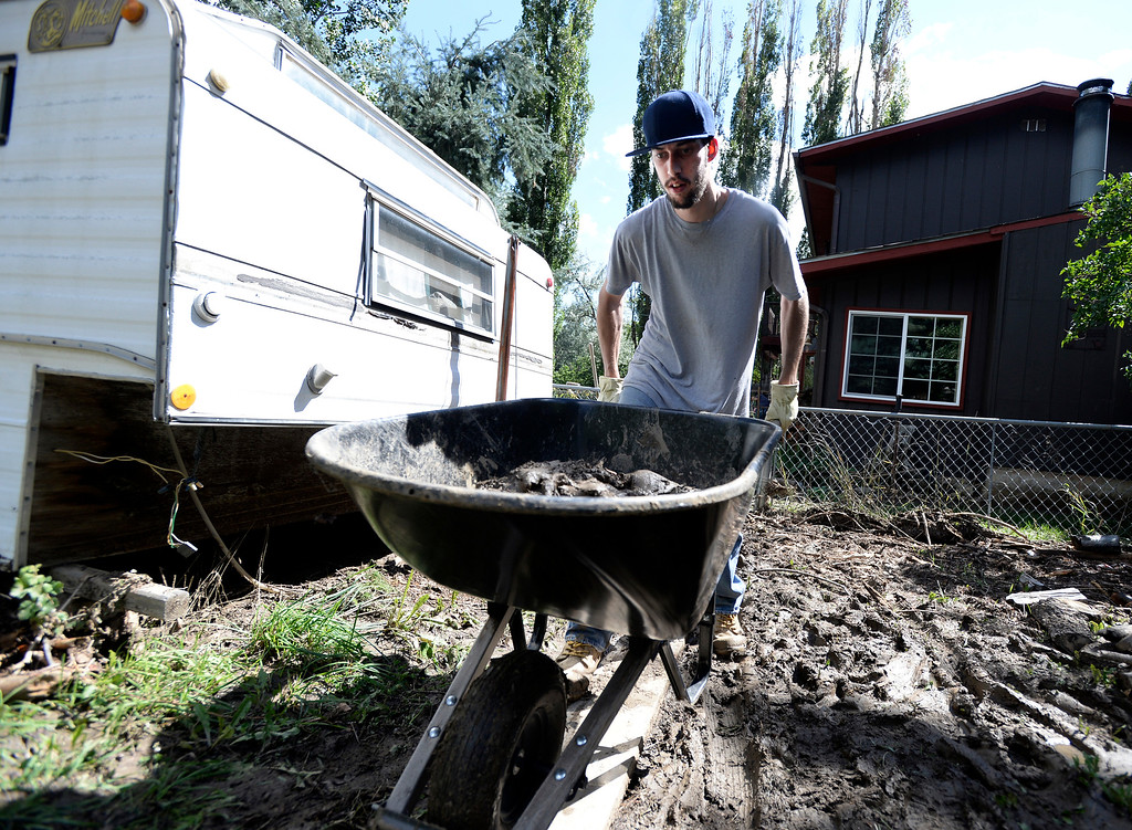 . Jestin Franklin pushes a wheelbarrow full of mud while helping his grandmother clean flood damage at her home on Tuesday, Sept. 17,  in the Fourmile Canyon area of Boulder County. For more photos and video of the flood rescue go to www.dailycamera.com Jeremy Papasso/ Camera