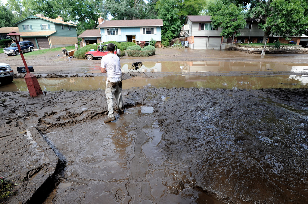 . Mark Swanson shovels out the mud from this home on Lefthand Drive in Longmont, Colorado, on September 14, 2013. Cliff Grassmick / September 14, 2013