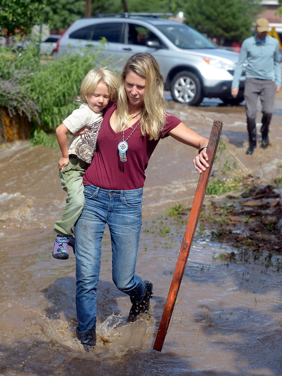 . Jessica Trusty carries her three-year-old son Leo through the floodwaters to her flooded home on Friday, Sept. 13, near 19th Street  in Boulder. For more photos and video of the flooding go to www.dailycamera.com Jeremy Papasso/ Camera
