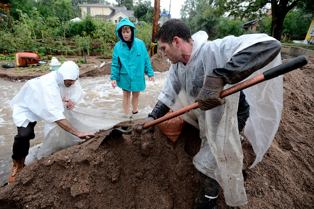 . Ed von Bleishert, shovels sand on a berm as Scott Hoffenberg pulls on plastic tarping as residents reinforce the dam on 7th Street on University Hill in Boulder, Colorado on Sunday September 15, 2013.  Rain fell heavily again today increasing fears of more flooding in the community. Susan Hendrickson looks on in the background.  Photo by Paul Aiken / The Daily Camera / Saturday September 15, 2013