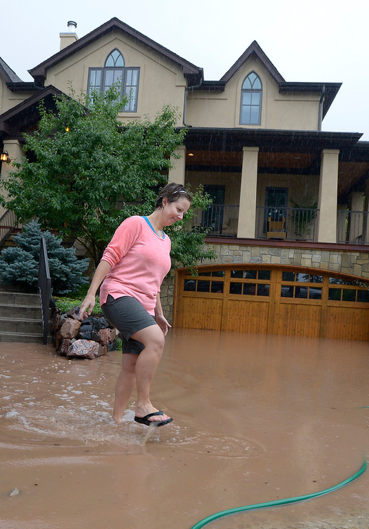 . Britt Drake, of Boulder, walks through her flooded driveway and home during the heavy flooding on Thursday in Boulder. For a video of the flooding go to www.dailycamera.com  Jeremy Papasso/ Camera