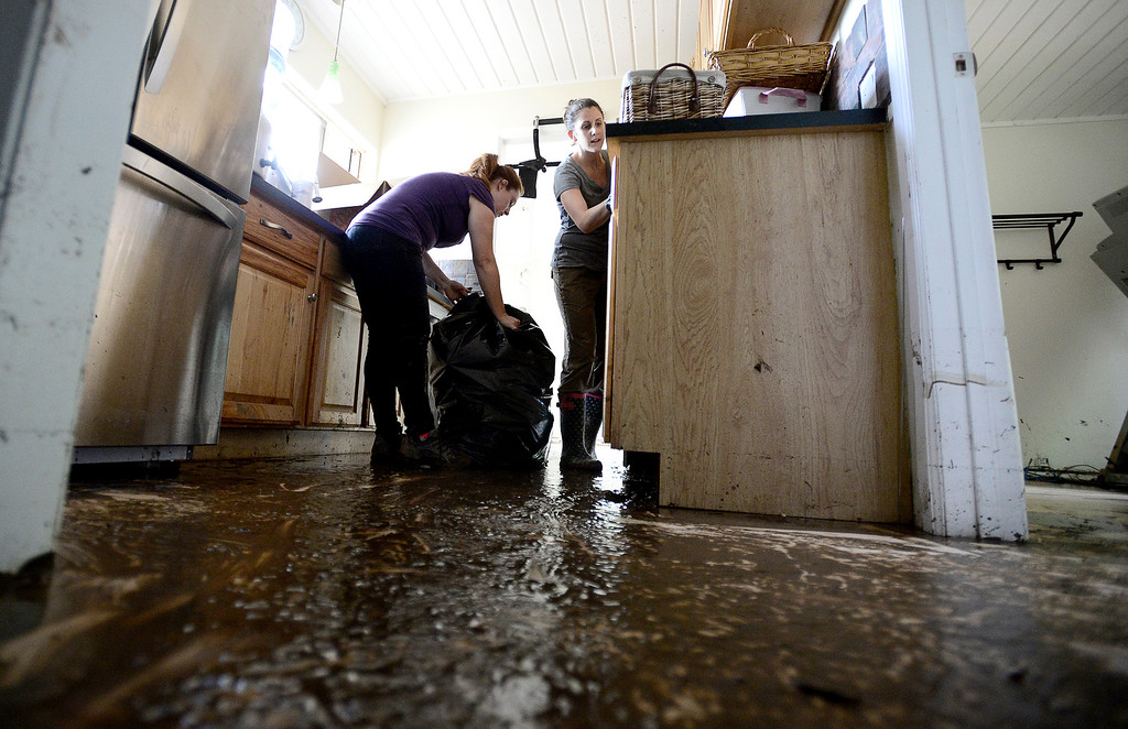 . Standing in a inch of mud, Lisa Mallen (right) and Shannon Aten (left) pack up what they can save from a friend\'s home on Gapter Road after heavy rains cause flooding in Boulder, Colorado September 14, 2013. BOULDER DAILY CAMERA/ Mark Leffingwell