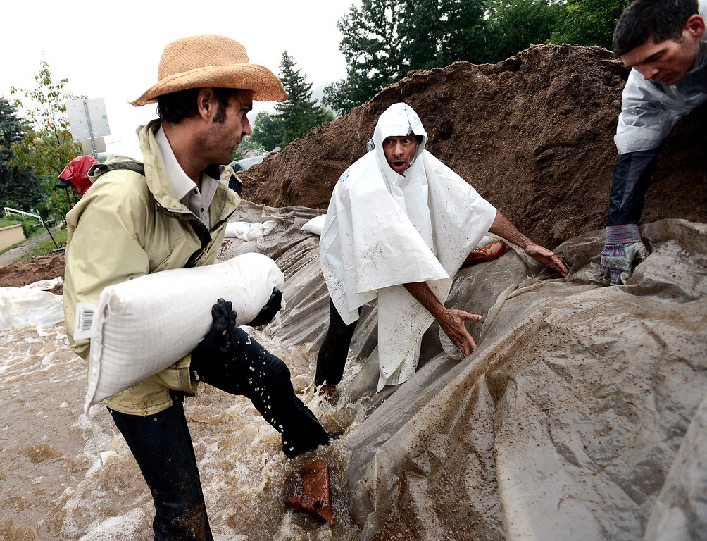 . Tim Eggert, left,  carries a sand bag as Scott Hoffenberg directs him as residents reinforce a berm on 7th Street on University Hill in Boulder, Colorado on Sunday September 15, 2013. Ed von Bleishert, right, holds plastic tarp on the berm. Rain fell heavily again today increasing fears of more flooding in the community. Photo by Paul Aiken / The Daily Camera / Saturday September 15, 2013